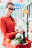 Woman holding a grocery basket royalty free stock photo