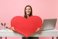 Young smiling woman showing on camera red empty blank heart sit work at white desk with pc laptop isolated on pastel. Pink background. Achievement business royalty free stock photography