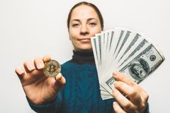 Young smiling woman shows Golden Bitcoin coin - symbol of cryptocurrency, new virtual money and stack of dollar bills royalty free stock photos