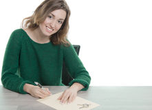 Young smiling woman signing paper Royalty Free Stock Images