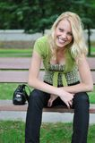 Young smiling woman siting on bench outdoors Royalty Free Stock Photos