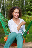 Young smiling woman sits in hammock with yellow flower she holds Royalty Free Stock Photo