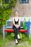 Young smiling woman sitting on the bench Royalty Free Stock Photos