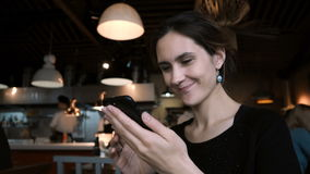 Young smiling woman sitting in cafe and using the smartphone. Attractive female chatting in social networks with friends. Happy girl typing message on stock video footage
