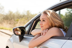 Young smiling woman sitting in car taking key Stock Photos
