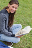 Young smiling woman sitting cross-legged in a park Stock Photo