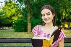 Young smiling woman sitting with diary making some notes in beautiful city park.  Stock Photo