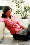 Young smiling woman sitting on the floor and using laptop Royalty Free Stock Photo
