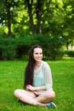 Young smiling woman sitting on grass. stock image