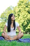 Young smiling woman sitting on rug in park Stock Photography
