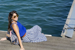 Young smiling   woman sitting on a sea pier in Barcelona Royalty Free Stock Photo