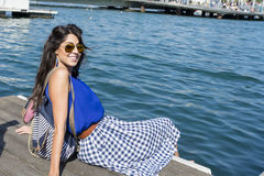 Young smiling   woman sitting on a sea pier in Barcelona Royalty Free Stock Images