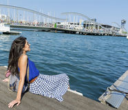 Young smiling   woman sitting on a sea pier in Barcelona Royalty Free Stock Image