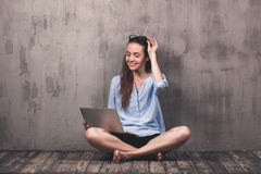 Young smiling woman sitting on the wooden floor with laptop Stock Image
