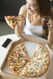 Young smiling woman with a slice of pizza Stock Photos
