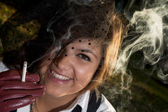 Young smiling woman smokes a cigarette Stock Photography