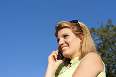 Young smiling woman speaks by mobile phone. Stock Photography