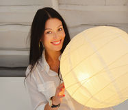 Young smiling woman standing near lamp , in the house Stock Image