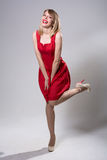 Young smiling woman standing on one leg in a red dress. Stock Image