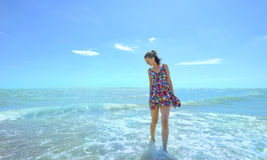Young smiling woman standing in sea waves and holding her dress Stock Images