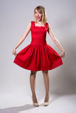 Young smiling woman standing while showing red dress Royalty Free Stock Photography