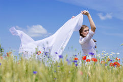 Young smiling woman standing in wheat field holding a white long piece of cloth in the wind. Royalty Free Stock Images