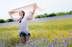 Young smiling woman standing in yellow wheat field holding a white shawl in the wind Stock Photo