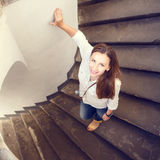 Young smiling woman stepping down at curved stairs Royalty Free Stock Photos