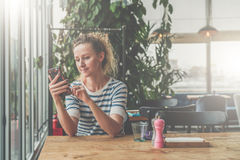 Young smiling woman in striped t-shirt is sitting in cafe at wooden table near window and using smartphone. Reading e-book. Girl shopping online, blogging Royalty Free Stock Image