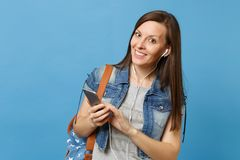 Young smiling woman student in denim clothes with backpack and earphones listening music holding using mobile phone stock photo