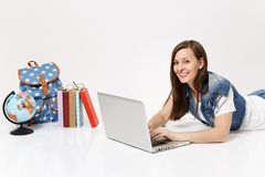Young smiling woman student in denim clothes working on laptop pc computer lying near globe backpack and school books. Isolated on white background. Education stock photography