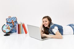 Young smiling woman student in denim clothes working on laptop pc computer lying near globe, backpack, school books. Isolated on white background. Education in stock photography