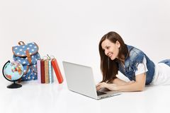 Young smiling woman student in denim clothes working on laptop pc computer lying near globe backpack and school books. Isolated on white background. Education stock images