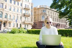 Young smiling woman student learning on-line via laptop computer, sitting on university campus. stock photo