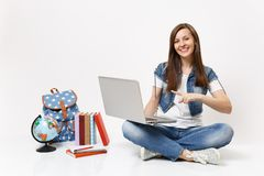 Young smiling woman student pointing index finger on laptop pc computer sitting near globe, backpack, school books. Isolated on white background. Education in royalty free stock image