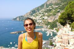 Young smiling woman with sunglasses and Amalfi village on the ba. Ckground. Picture of female tourist in her summer holidays in Southern Italy stock photography