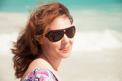 Young smiling woman in sunglasses on a beach Royalty Free Stock Photography