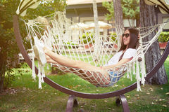 Young smiling woman in sunglasses resting in hammock in backyard Royalty Free Stock Image
