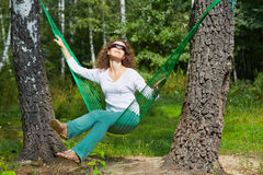 Young smiling woman in sunglasses sits in hammock Stock Image