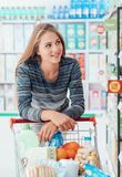 Young woman at the supermarket. Young smiling woman at the supermarket, she is shopping and pushing a cart along the store aisles Royalty Free Stock Images