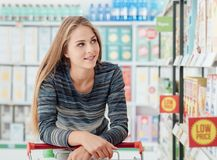 Young woman at the supermarket. Young smiling woman at the supermarket, she is shopping and pushing a cart along the store aisles Royalty Free Stock Photos