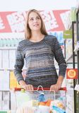Young woman at the supermarket. Young smiling woman at the supermarket, she is shopping and pushing a cart along the store aisles Stock Photo