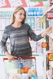 Young woman at the supermarket. Young smiling woman at the supermarket, she is shopping and pushing a cart along the store aisles Stock Image