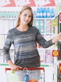 Young woman at the supermarket. Young smiling woman at the supermarket, she is shopping and pushing a cart along the store aisles Stock Photography