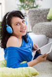 Young smiling  woman with tablet   and headphones at home Stock Photos