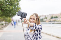Young smiling woman takes photo her smart phone in the street. Royalty Free Stock Photos