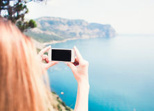 Young smiling woman taking travel photo on trekking excursion day - Hipster girl taking photo at view point with blue ocean backgr Royalty Free Stock Image