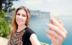 Young smiling woman taking travel selfie on trekking excursion day - Hipster girl taking self photo at view point with blue ocean. Background - Concept of Stock Image