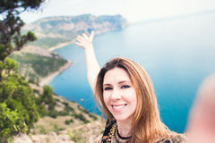 Young smiling woman taking travel selfie on trekking excursion day - Hipster guy self photo at view point with blue ocean backgrou Royalty Free Stock Photography