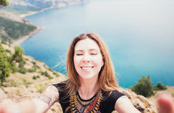 Young smiling woman taking travel selfie on trekking excursion day - Hipster guy self photo at view point with blue ocean backgrou Stock Image